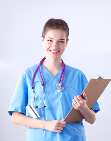 pretty young girl: Smiling female doctor with a folder in uniform standing