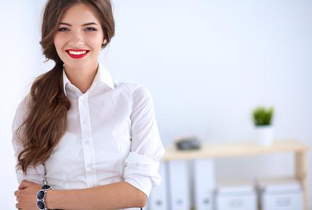 mujer alegre: Atractivo de negocios de pie cerca de la pared en el cargo.