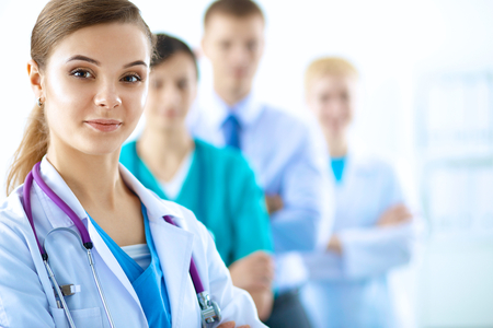 health care: Attractive female doctor in front of medical group .