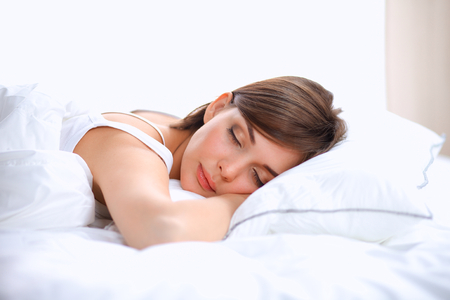 woman only: Beautiful girl sleeps in the bedroom, lying on bed. Stock Photo