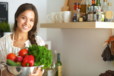 liveliness: Smiling young woman holding vegetables standing in kitchen .