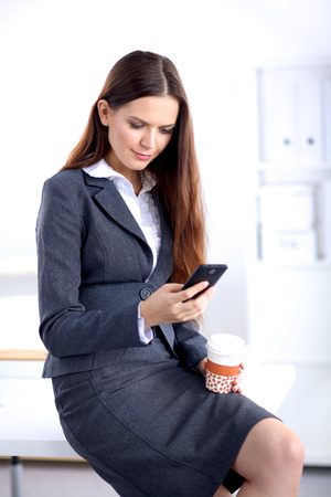 message sending: Businesswoman sending message with smartphone sitting