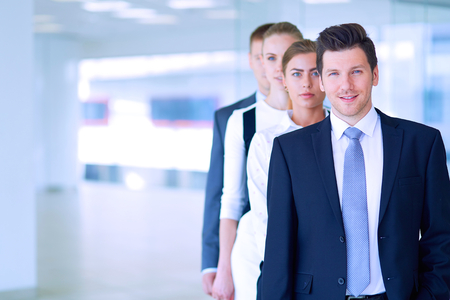 merchant: Smiling successful business team standing in office . Stock Photo
