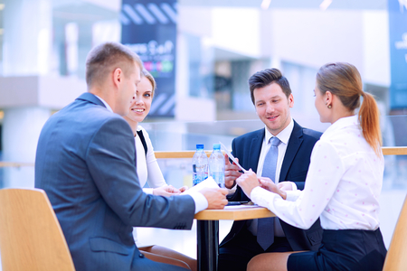 working: Group of happy young business people in a meeting at office .