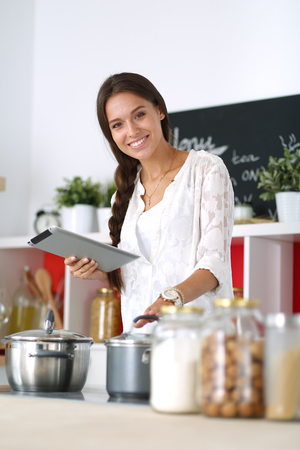 tab: Young woman using a tablet computer to cook in her kitchen
