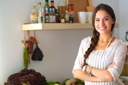 Młoda kobieta, stojąca w pobliżu biurku w kuchni. Zdjęcie Seryjne
