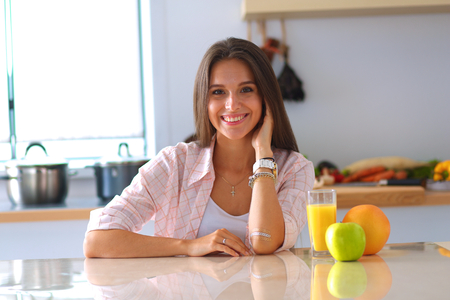 natural: Young woman sitting near desk in the kitchen .