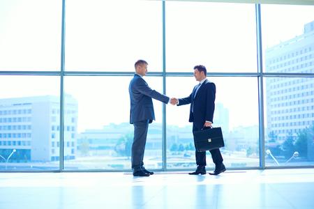 お互い手を振って 2 つの成功するビジネス男性の完全な長さのイメージ。