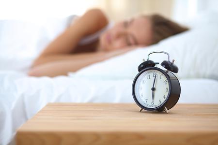 若い女性と自宅の寝室で目覚まし時計を眠っています。