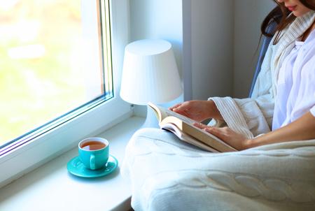 Młoda kobieta w domu siedzi obok okna relaks w jej salonie czytanie książki i picia kawy lub herbaty.