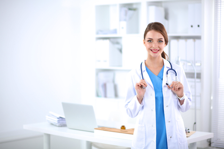 health professionals: Portrait of young woman doctor with white coat standing in hospital . Stock Photo