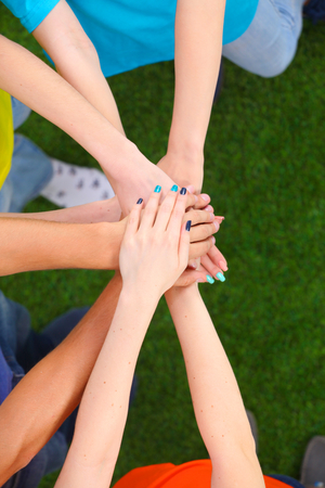 unanimous: People joining their hands on green grass Stock Photo