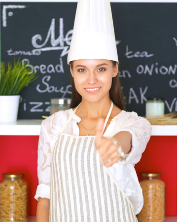 culinary skills: Chef woman portrait with uniform in the kitchen and showing ok