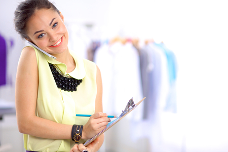 paying attention: Pretty fashion designer working in office using mobile phone