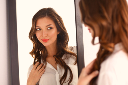 Jeune femme se regardant dans le miroir de réflexion à la maison. Banque d'images - 51419528