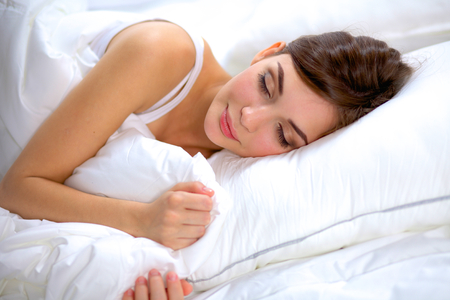 only one young adult woman: Beautiful girl sleeps in the bedroom, lying on bed. Stock Photo