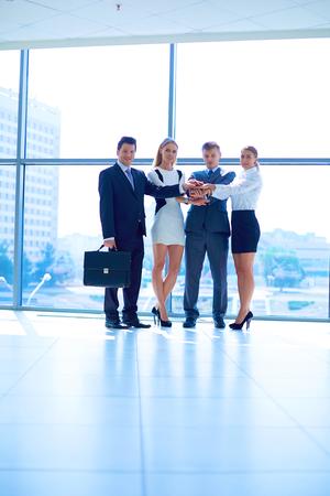 Empresarios con sus manos juntas en un círculo
