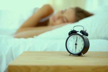 awaking: Young sleeping woman and alarm clock in bedroom at home .