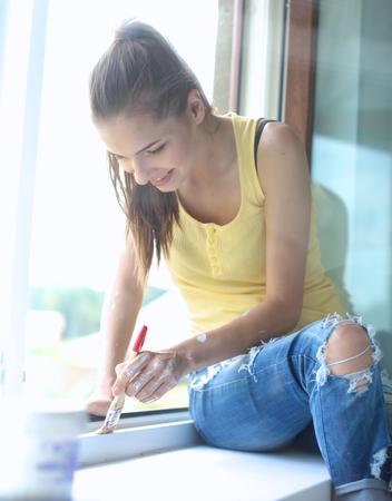 brocha de pintura: Mujer con un pincel acabado cuidadosamente de alrededor de un marco de ventana