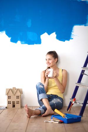 housepainter: Portrait of female painter sitting on floor after painting.