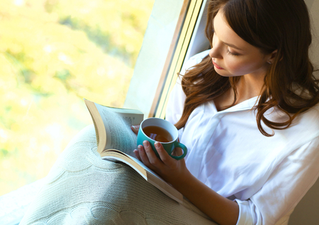 drinking: Young woman at home sitting near window relaxing in her living room reading book and drinking coffee or tea .
