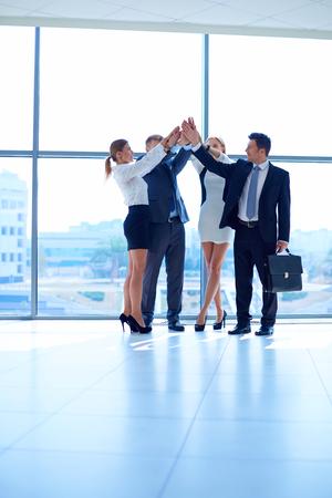mujeres juntas: La gente de negocios con sus manos juntas en un círculo.