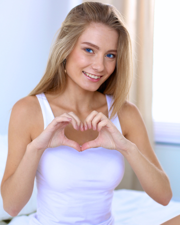 Beautiful woman showing heart shape on her hand , sitting  bed.
