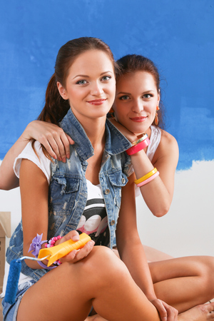 housepainter: Two Beautiful young woman doing wall painting, sitting. Stock Photo