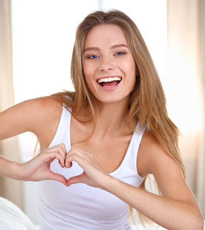 to tease: Beautiful woman showing heart shape on her hand , sitting  bed.