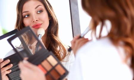 Young beautiful woman making make-up near mirror .