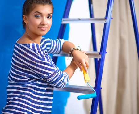 housepainter: Beautiful young woman doing wall painting, standing near ladder Stock Photo