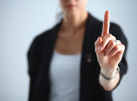 imaginary: Woman touching an imaginary screen with her finger .