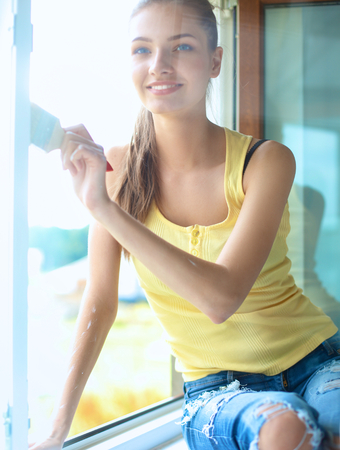 paintbrush: Woman with a paintbrush carefully finishing off around a window frame
