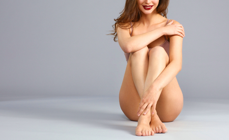 shapely legs: Beautiful barefoot woman sitting on the floor .