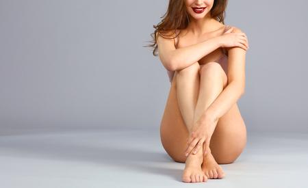 ropa interior niñas: Mujer descalza hermosa que se sienta en el suelo. Foto de archivo