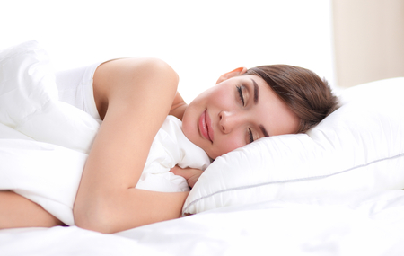 Beautiful girl sleeps in the bedroom, lying on bed. Stock Photo