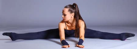 sports clothing: Young attractive female fitness woman performing a twine .