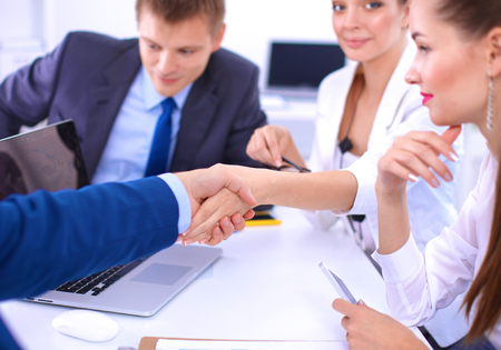 unanimous: Business people shaking hands, finishing up a meeting, in office. Stock Photo