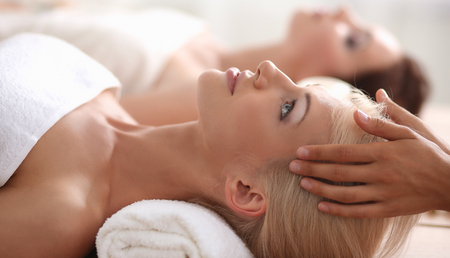 skin treatment: Two young beautiful women relaxing and enjoying at the spa Stock Photo