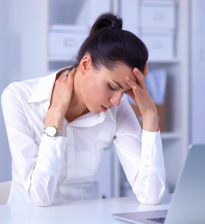 cabeza femenina: Empresaria tensionada sentado en el escritorio, aislado en blanco
