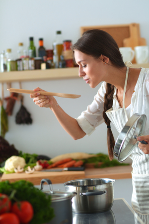 woman cooking: Cooking woman in kitchen with wooden spoon.