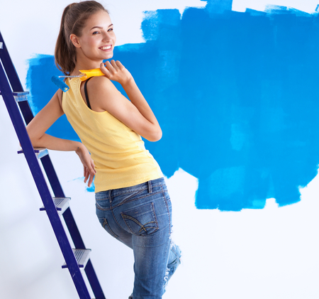 housepainter: Beautiful young woman doing wall painting, standing on ladder