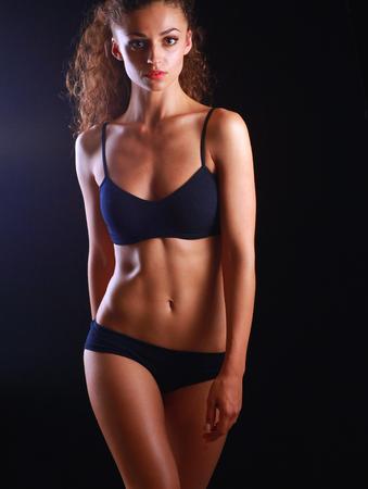 poses de modelos: Retrato de mujer joven y hermosa gimnasio, aislado sobre fondo negro. Foto de archivo