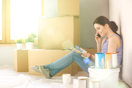 paint swatch: Woman choosing paint colour from swatch for new home sitting on wooden floor. Stock Photo