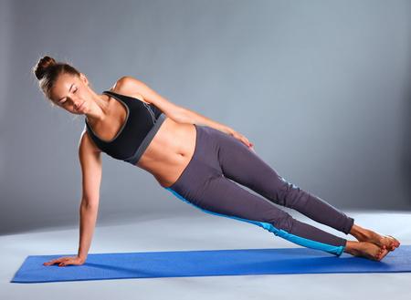 estiramiento: Retrato de la muchacha del deporte que hace yoga ejercicio de estiramiento.