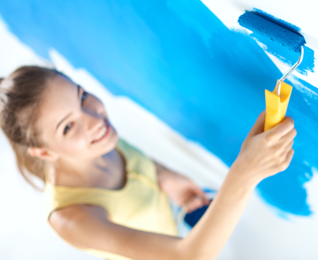 housepainter: Beautiful young woman doing wall painting Stock Photo
