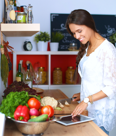 joy pad: Young woman using a tablet computer to cook in her kitchen .