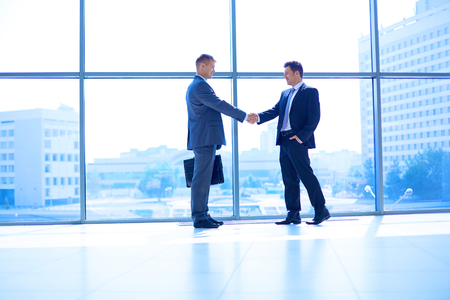 Imagem cheia do comprimento de dois homens de neg�cios bem sucedidos apertando as m�os uns com os outros.