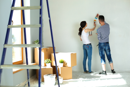 renovating: Portrait of happy smiling young couple  painting interior wall of new house.