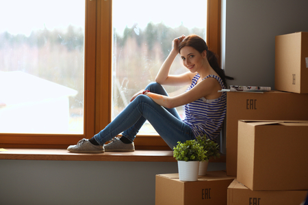 female sexuality: Girl sitting on windowsill at new home. Stock Photo